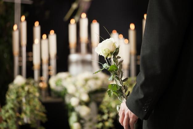 葬儀で白い花を保持している女性 Premium写真