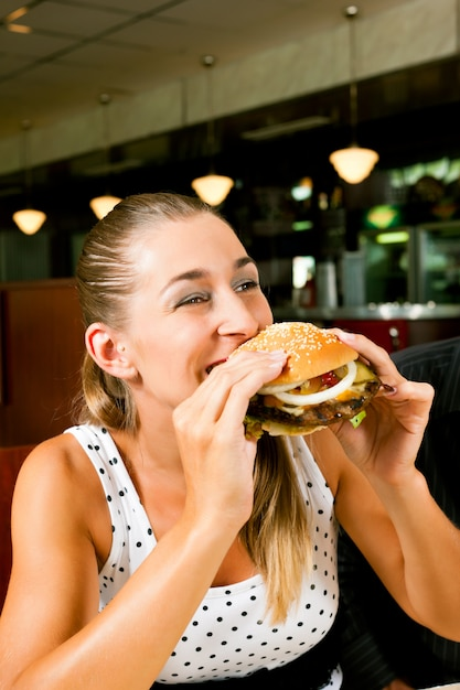 Женщина в ресторане ест гамбургер Premium Фотографии