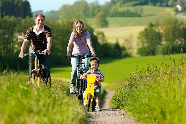 Семья катается на велосипедах летом Premium Фотографии