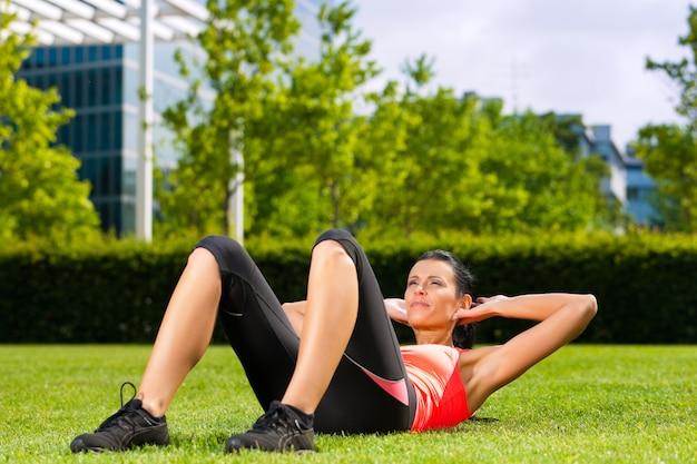 都市スポーツ-草の上のウォーミングアップの女性 Premium写真