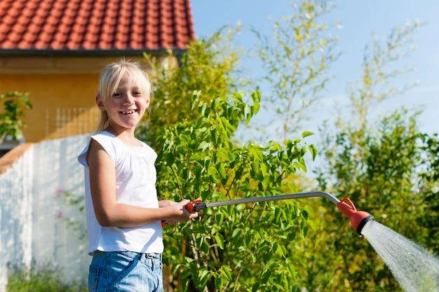 Улыбающаяся девушка поливает растения в саду Premium Фотографии