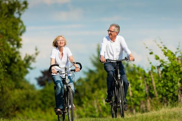 自然の中で自転車に乗って幸せな成熟したカップル Premium写真