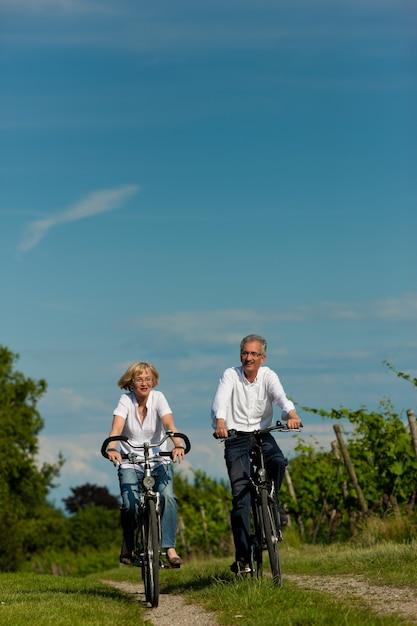 中年のカップルが夏の田舎道でサイクリング Premium写真