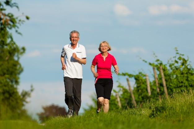田舎道に沿ってジョギングアクティブシニアカップル Premium写真