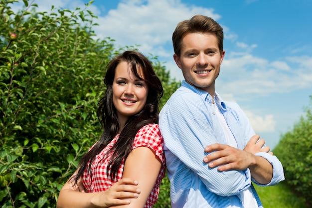 果樹園でポーズをとって笑顔のカップル Premium写真