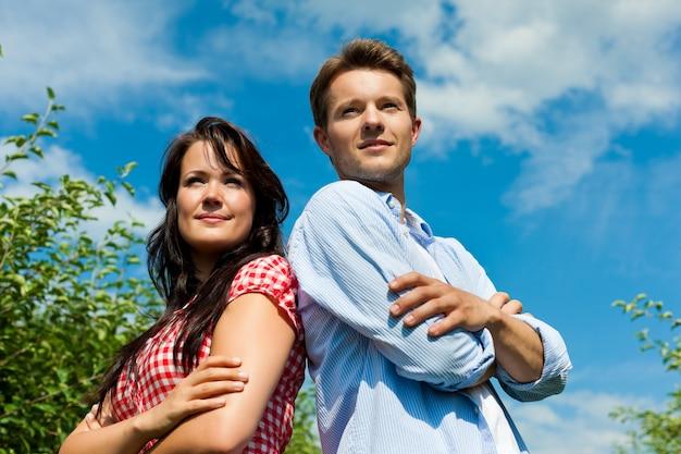 遠くを見ている果樹園でポーズのカップル Premium写真