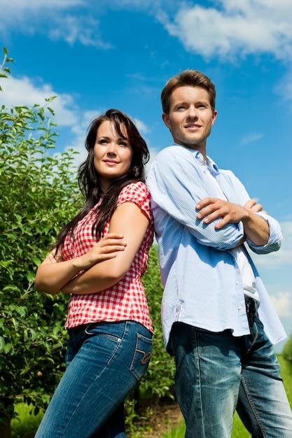 組んだ腕でポーズをとって果樹園のカップル Premium写真