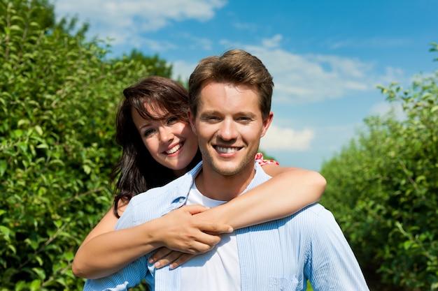 陽気な果樹園でポーズをとるカップル Premium写真