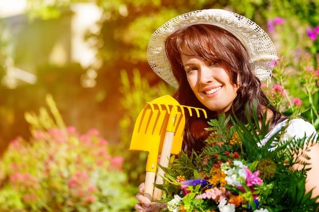 Женщина садовник с цветами в солнечном саду Premium Фотографии