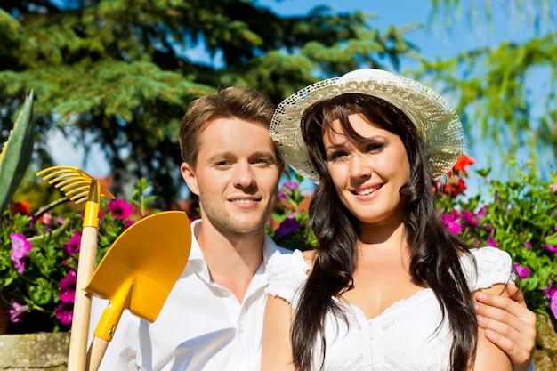 ガーデニングツールと花の前でポーズのカップル Premium写真