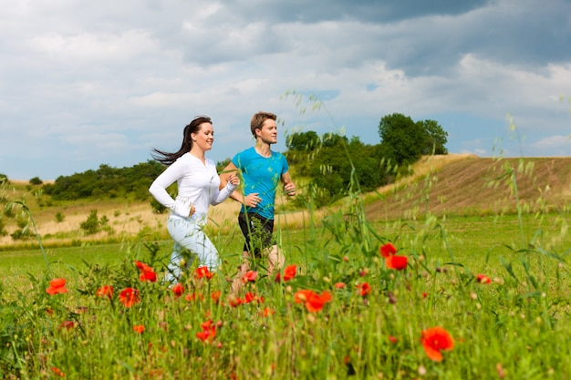 若い陽気なカップルは外でジョギングします。 Premium写真