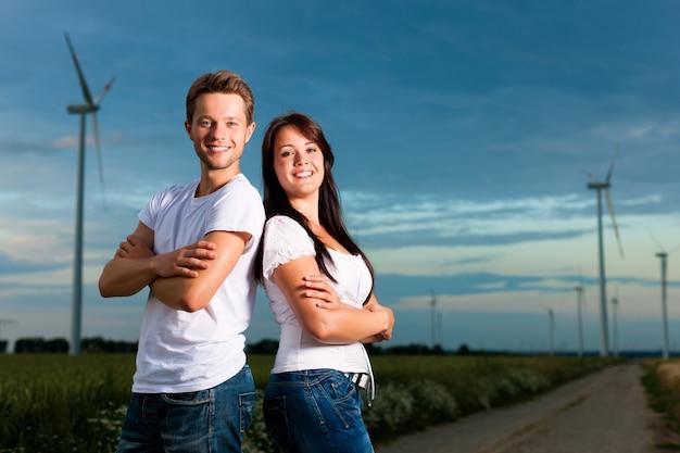 腕を組んで風車の前でポーズ陽気なカップル Premium写真