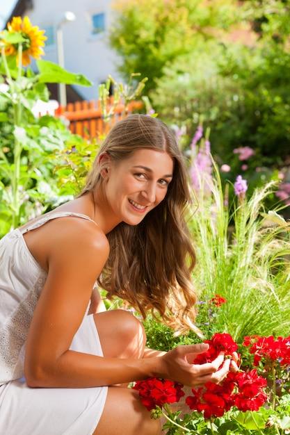 Сад летом - счастливая женщина с цветами Premium Фотографии