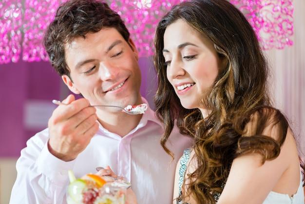アイスクリームパーラーで自分の時間を楽しんでいる若いカップル Premium写真