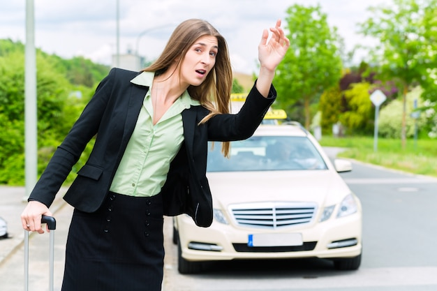 Молодая коммерсантка вызывает такси Premium Фотографии