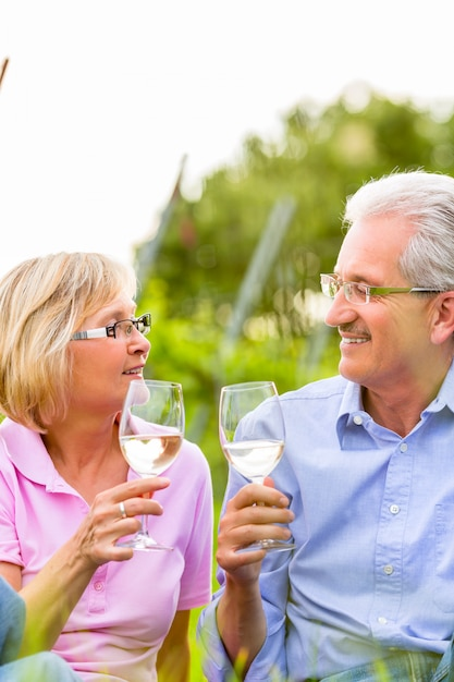 ワインを飲んでピクニックを持つ幸せな先輩 Premium写真