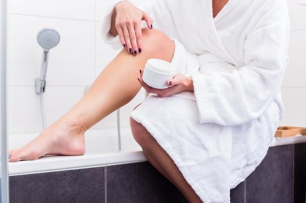 Женщина сидит на краю ванны, надевая лосьон на ноги Premium Фотографии