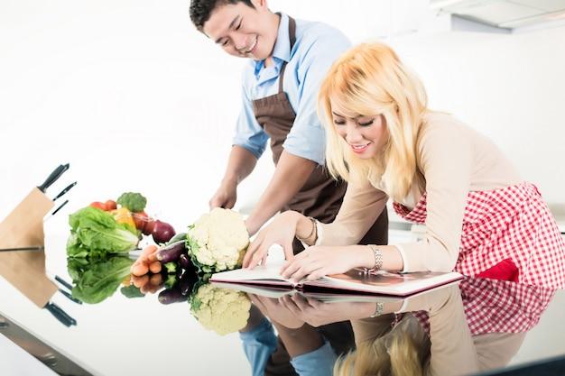 料理本でレシピを読むアジアカップル Premium写真