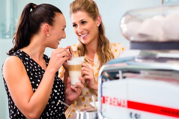 ガールフレンドのコーヒーバーでラテマキアートを飲む Premium写真