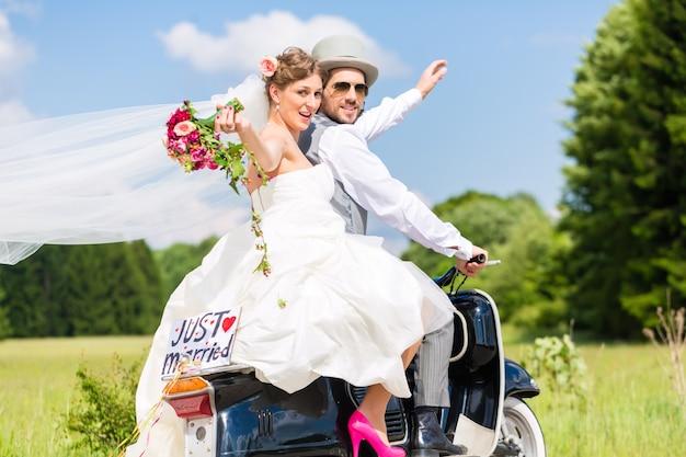 モータースクーターの結婚式のカップルはちょうど結婚した Premium写真