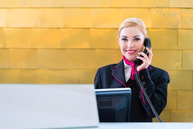 フロントデスクに電話でホテルの受付係 Premium写真