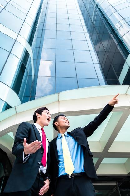 高層ビルの前でアジアのビジネスマン Premium写真