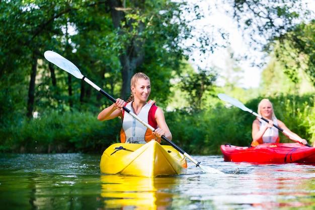 森の川でカヌーを漕ぐ女性 Premium写真