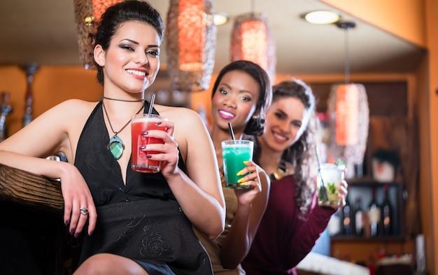 カクテルを飲みながら、クラブでナイトライフを楽しむ女の子 Premium写真