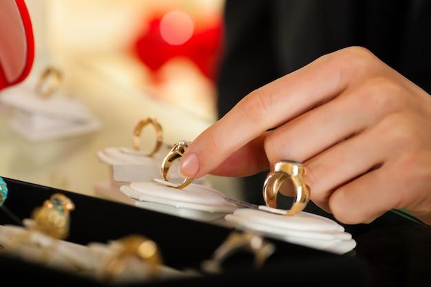 宝石商でリングを選ぶカップル Premium写真