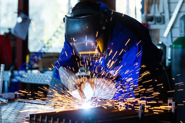 Сварщик сваривает металл в мастерской с искрами Premium Фотографии
