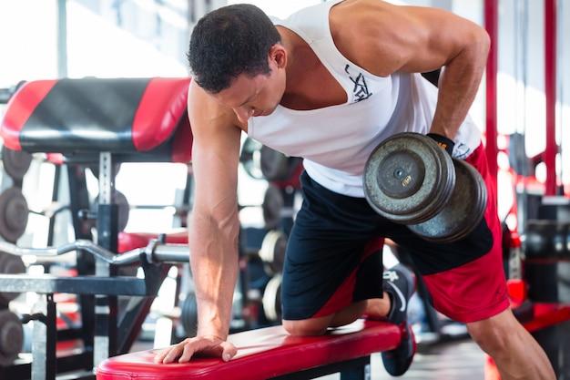 フィットネスジムでスポーツでダンベルを持つ男 Premium写真