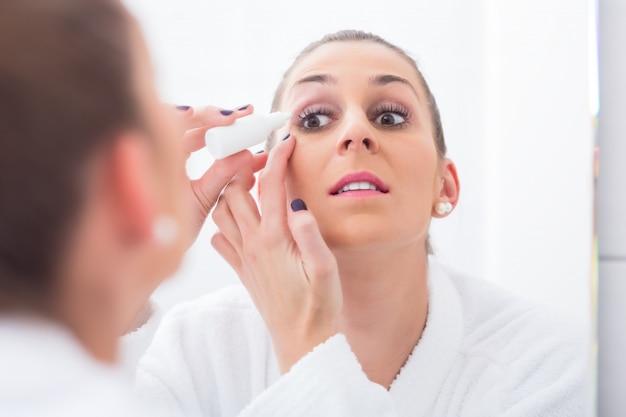 点眼薬を適用する女性 Premium写真
