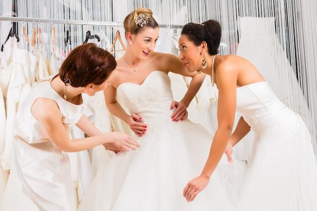 お店でフィッティングブライダルドレス中に楽しんでいる女性 Premium写真