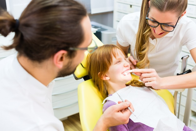 歯科手術で女の子治療を与える歯科医 Premium写真