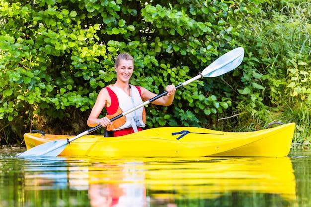女性の森の川でカヤックで運転 Premium写真