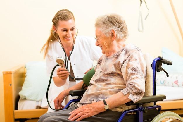 若い看護師と特別養護老人ホームの女性シニア Premium写真