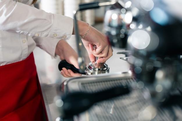 Официант готовит эспрессо на автоматической кофемашине Premium Фотографии
