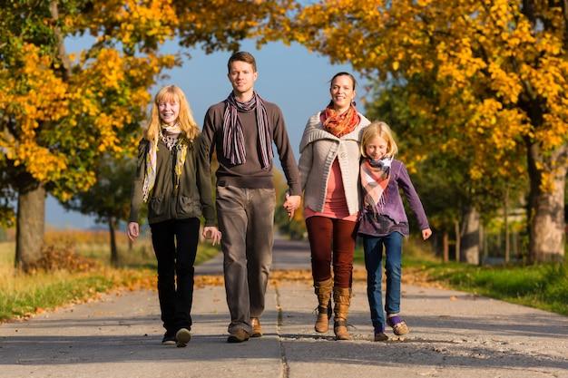 秋の色鮮やかな木々の前を歩く家族 Premium写真