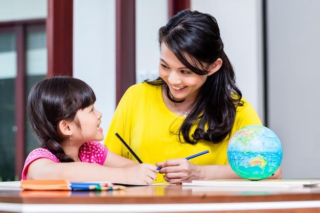 子供と学校の宿題をしている中国人の母親 Premium写真