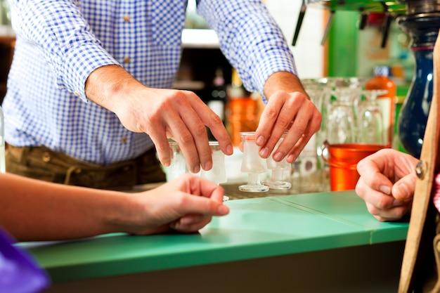 グラスに硬い酒を注ぐバーキーパー Premium写真