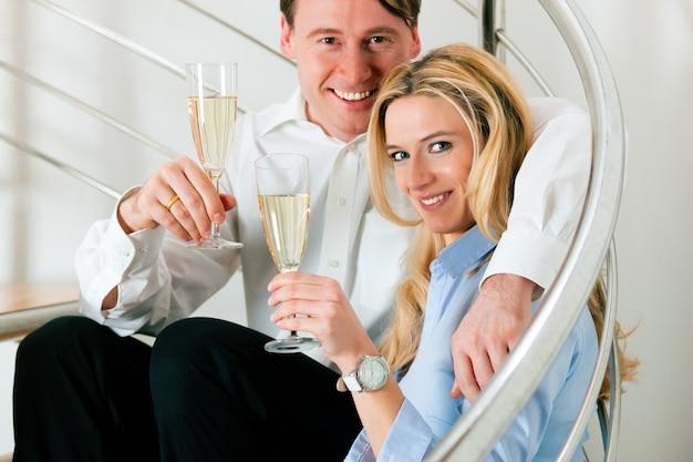 シャンパンで自宅でビジネスカップル Premium写真