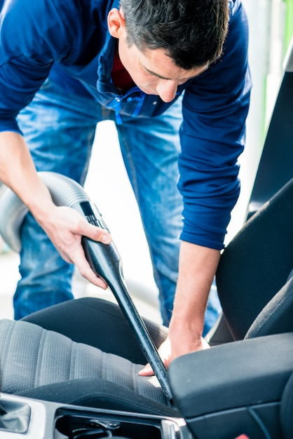若い男が車の内部を掃除するための真空を使用して Premium写真