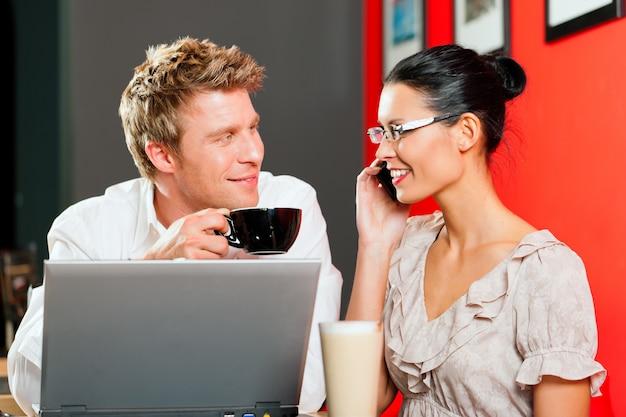 ノートパソコンとモバイルのコーヒーショップのカップル Premium写真