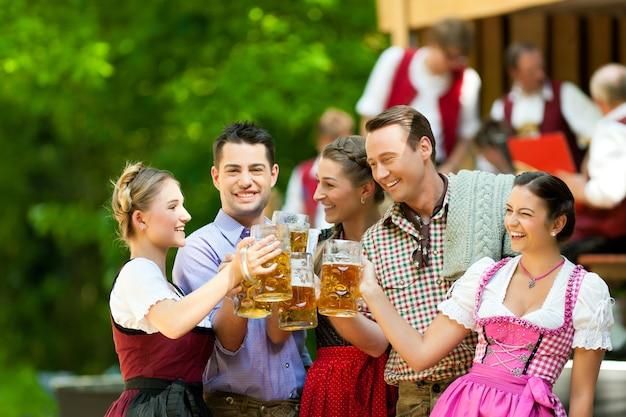 ビールを飲む友人とオクトーバーフェストパーティー Premium写真