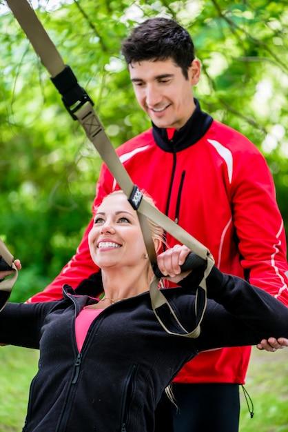 スリングトレーニングでトレーナーとスポーツの女性 Premium写真