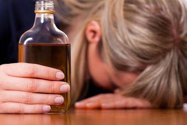 アルコール乱用-ブランデーを飲みすぎている女性 Premium写真