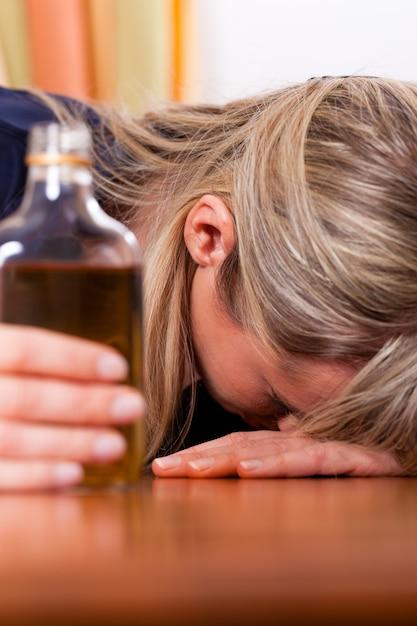 Злоупотребление алкоголем - женщина пьет слишком много бренди Premium Фотографии