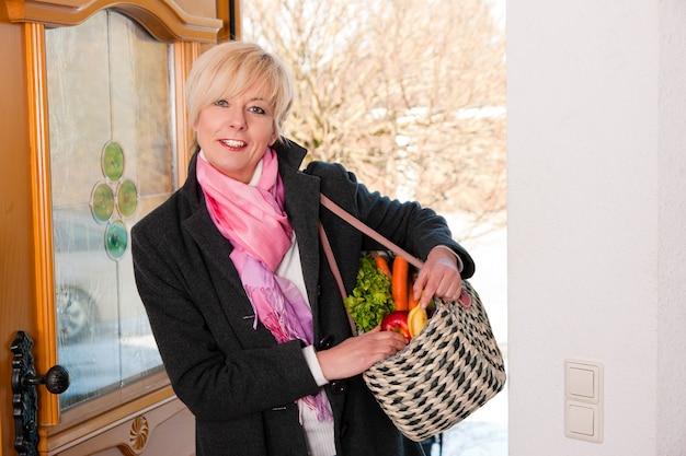 彼女の食料品を持つ女性 Premium写真
