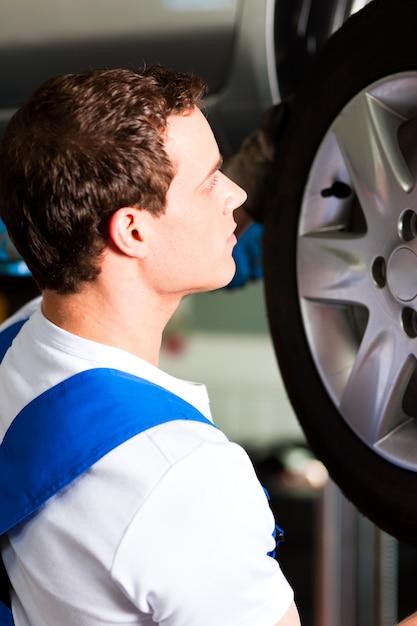 タイヤを変更するワークショップの自動車修理工 Premium写真