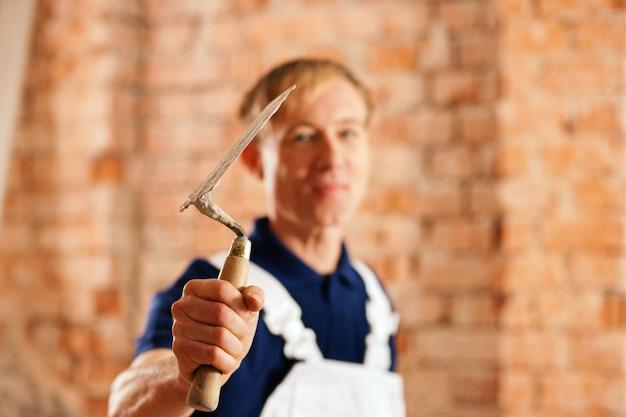 Каменщик с мастерком на строительной площадке Premium Фотографии